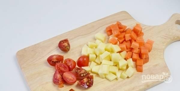 Пока суп закипает, займитесь оставшимися овощами. Почистите картофель и морковь. Вымойте их вместе с помидорами. Нарежьте морковку и картошку на кубики среднего размера, а томаты разделите на дольки.