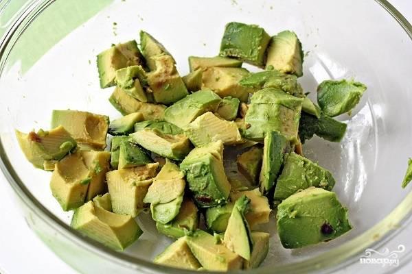 2. Для начала вымойте, обсушите и очистите авокадо. Удалите косточку, а мякоть нарежьте средними кубиками. При желании можете сразу взбрызнуть свежевыжатым соком лимона.
