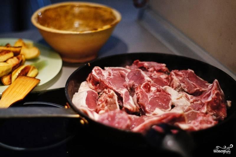 Лук достаньте, выложите в сковороду баранину, порезанную на куски.