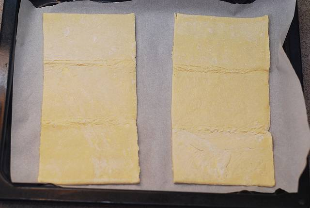 2. Слоеное тесто нужно достать заранее, чтобы оно подтаяло. Выложить его сразу на пергамент для выпечки и оставить примерно на 25-30 минут.
