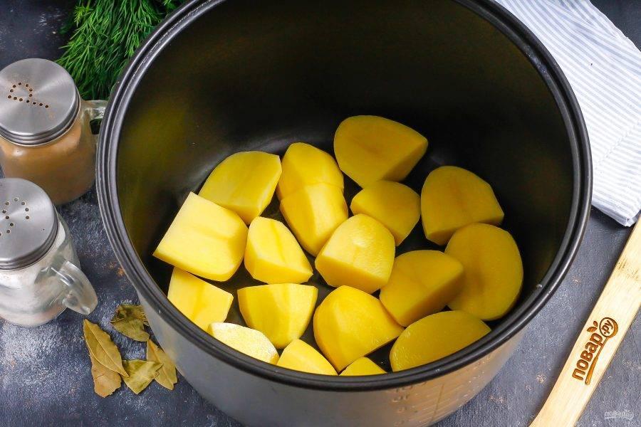 Очищенный картофель нарежьте крупными кусочками или разрежьте пополам, если он не слишком крупный. Выложите в чашу мультиварки.