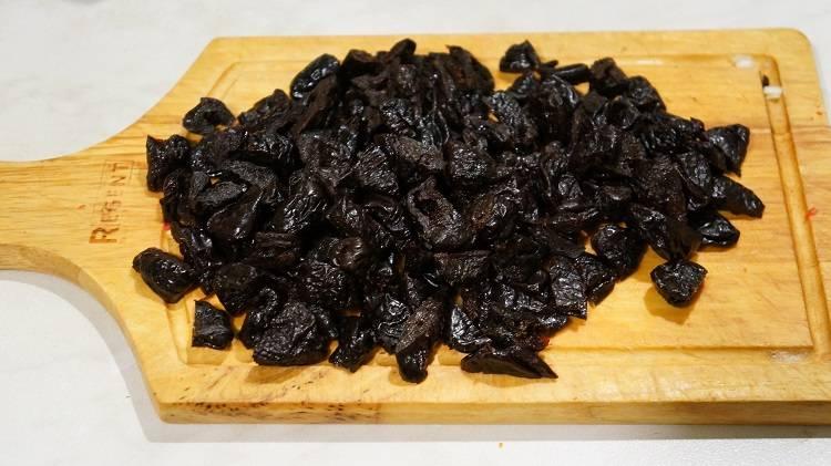 Добавляем к мясу по 2 чайные ложки сушеного базилика, петрушки, чёрного перца.  Дальше преступаем к черносливу. Чернослив я взяла в банке, который уже вымыт, просушен и в нем нет косточек.  Поэтому чернослив остается только порезать примерно одну черносливинку на две-три равные части. Если же чернослив взяли с косточками, то надрезая каждую ягодку, достаньте косточки и также порежьте чернослив.