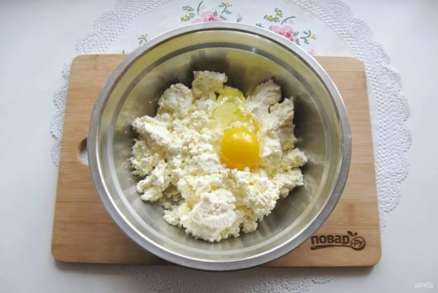 Приготовьте начинку для пирога. В миску выложите творог и добавьте яйцо.