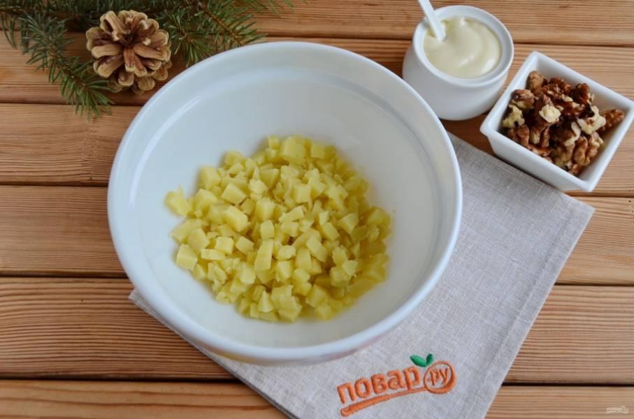 2. Картофель порежьте небольшими кубиками и сложите в чистый салатник.