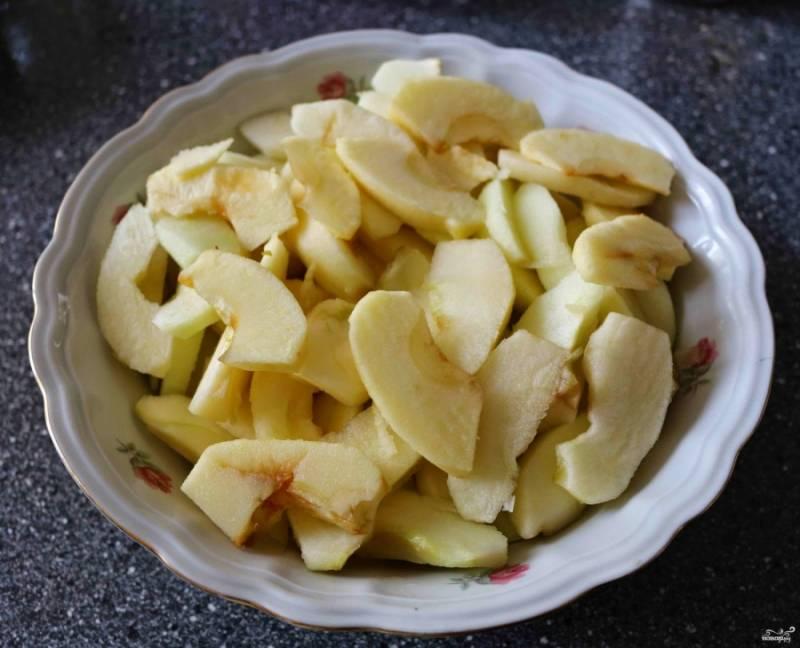Крупные яблоки вымойте и удалите с них кожуру. Затем нужно вынять из яблока сердцевину и нарезать его на некрупные дольки. К яблокам добавьте лимонный сок, стакан сахара и корицу.