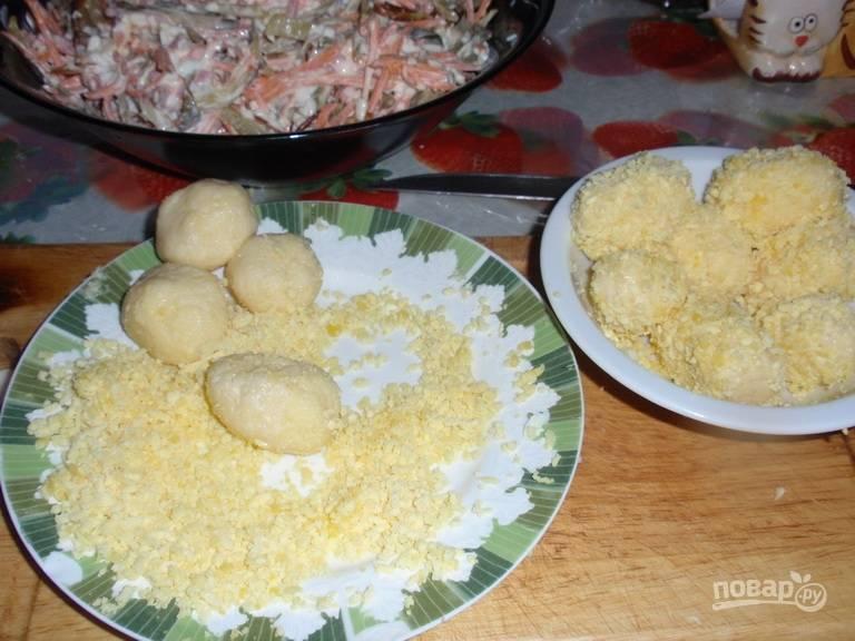 Из сырной массы сформируйте овалы в форме небольших яиц. Каждый из них обваляйте в желтках.
