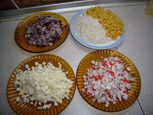 Отварить рис и яйца. Крабовые палочки, лук, яйца мелко нарезать. Сыр натереть на мелкой терке.