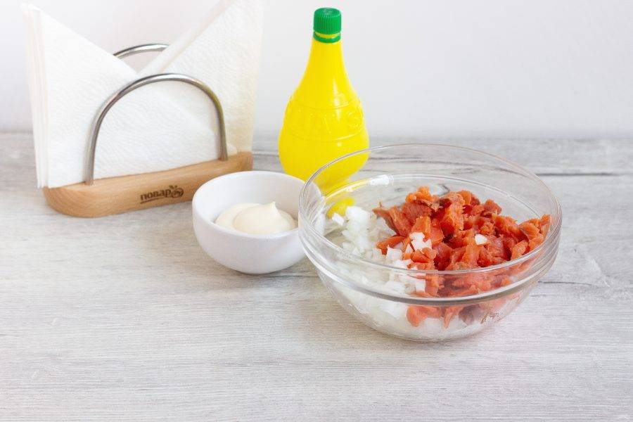 Рыбу и лук мелко нарежьте, заправьте лимонным соком и майонезом. Поперчите по вкусу и хорошо перемешайте.