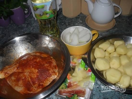 В первую очередь маринуем курицу в смеси растительного масла, специй для курицы. Туда же добавим пол чайной ложки соли. Очистим картофель и лук.