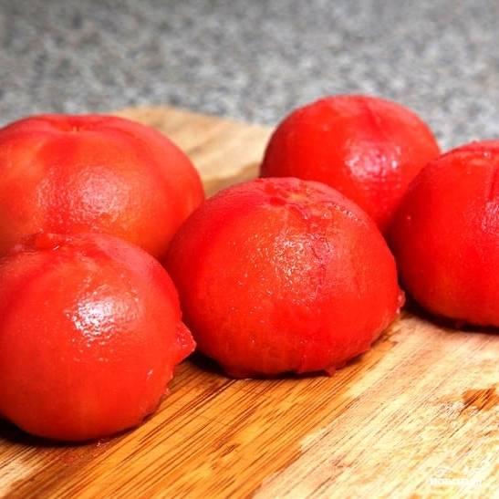 Сразу вслед за этим окатываем помидоры холодной водой и снимаем с них кожицу.