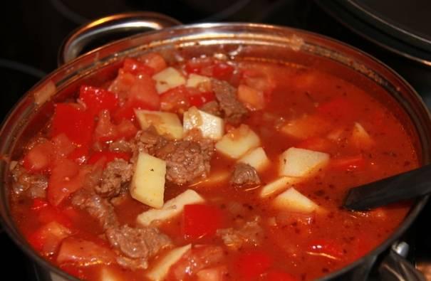 Чистим картофель, у перцев удаляем сердцевину с семенами. Нарезаем и перцы, и картофель мелкими кубиками и добавляем в гуляш. Варим еще минут 25-30 на медленном огне. В конце можно добавить полстакана красного сухого вина и дать гуляшу еще покипеть минут 5.