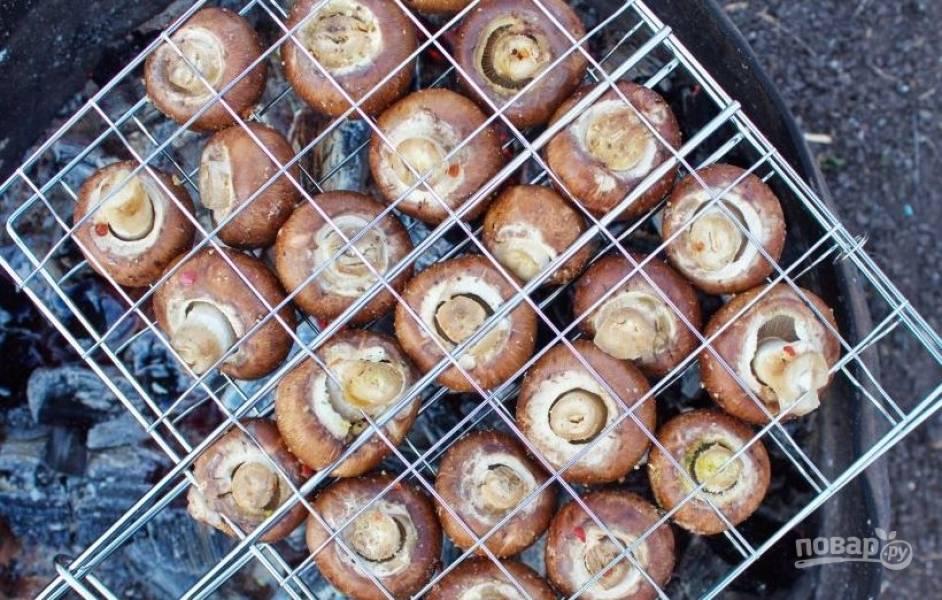 Замаринованные грибы выложите на решетку так, чтобы между ними были просветы. Обжаривайте грибы около десяти минут, периодически переворачивая со одной стороны на другую.
