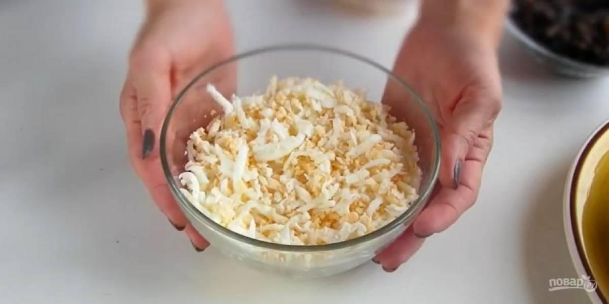 2. Выложите слой куриного филе на блюдо, сверху нарисуйте сеточку из майонеза. Далее выложите натертые на крупной терке 5 отварных яиц и 2 белка (желтки оставьте для украшения).