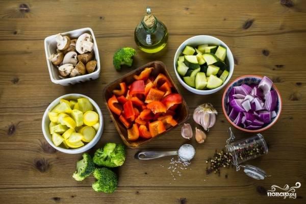 Овощи и грибы промойте под проточной водой. Лук очистите от кожицы, из перца удалите сердцевину и семена. Все овощи и шампиньоны нарежьте кусочками приблизительно одинакового размера.