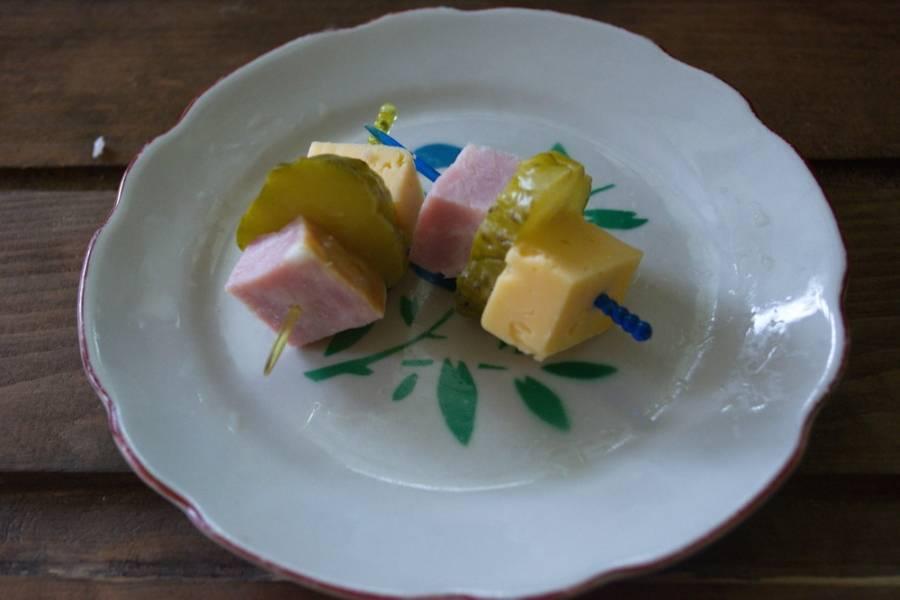 На каждую шпажку нанизайте по кусочку сыра, ветчины и огурчика.