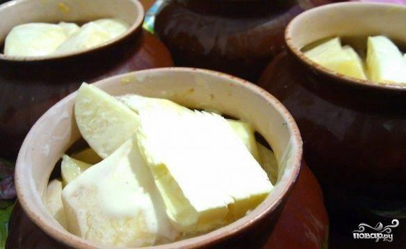 Выложить сверху оставшуюся картошку. Залить сметаной с водой так чтобы уровень жидкости был на 2 пальца ниже картофеля. Сверху положить по кусочку сливочного масла.