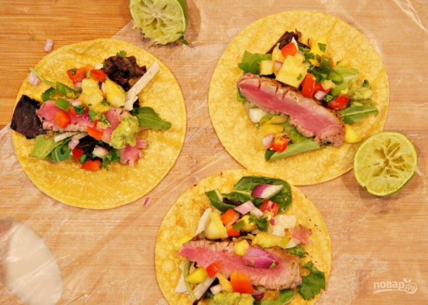 Я подаю салат на кукурузных лепешках. На лепешку выкладываю сначала овощи, а затем кладу тоненький кусочек тунца.