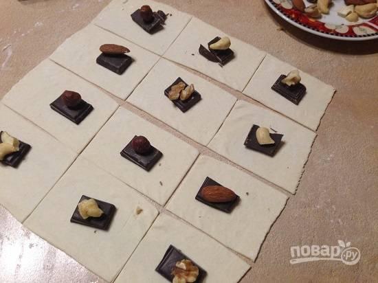 2. Лист теста раскатываем, чтобы по размеру он стал примерно в два раза больше своего первоначального размера. Разрезаем на 12 частей, в центр каждой выкладываем по квадратику шоколада и по орешку.