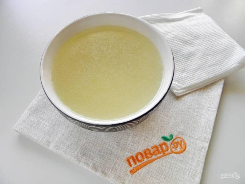 Готовый бульон попробуйте на соль, отцедите через несколько слоев марли. Бумажными салфетками промокните жир с поверхности, он легко удаляется. Добавьте желатин из расчета 1 ст.л на 350 мл жидкости. Растворите его.