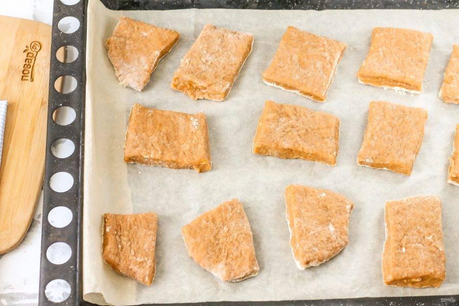 После чего застелите противень пергаментной бумагой. Раскатайте пряничное тесто на рабочей поверхности и нарежьте его кубиками или вырежьте фигурки вырубкой. Поместите их на бумагу. Разогрейте духовку до 180 градусов и поместите противень в духовку. Выпекайте пряники около 15 минут.