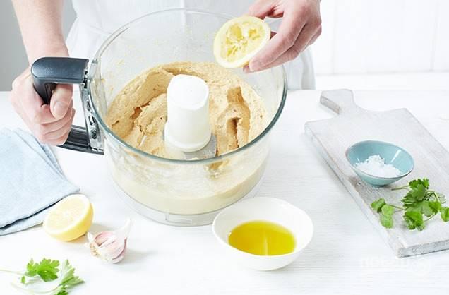 3. В это время сделайте хумус. В чашу блендера поместите 100 грамм нута, 3 ч.л. воды, добавьте 1 зубчик чеснока, сок половины лимона, 3 столовые ложки оливкового масла, соль, немного петрушки и кориандра. Измельчите все до гладкой консистенции, при необходимости добавьте воду.