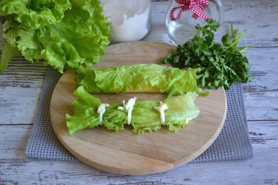 Сверните блинчик, оберните каждый в отдельный листочек салата. С помощью сырной косички, которую предварительно разделайте на отдельные волокна, завяжите блин примерно на одинаковом расстоянии.