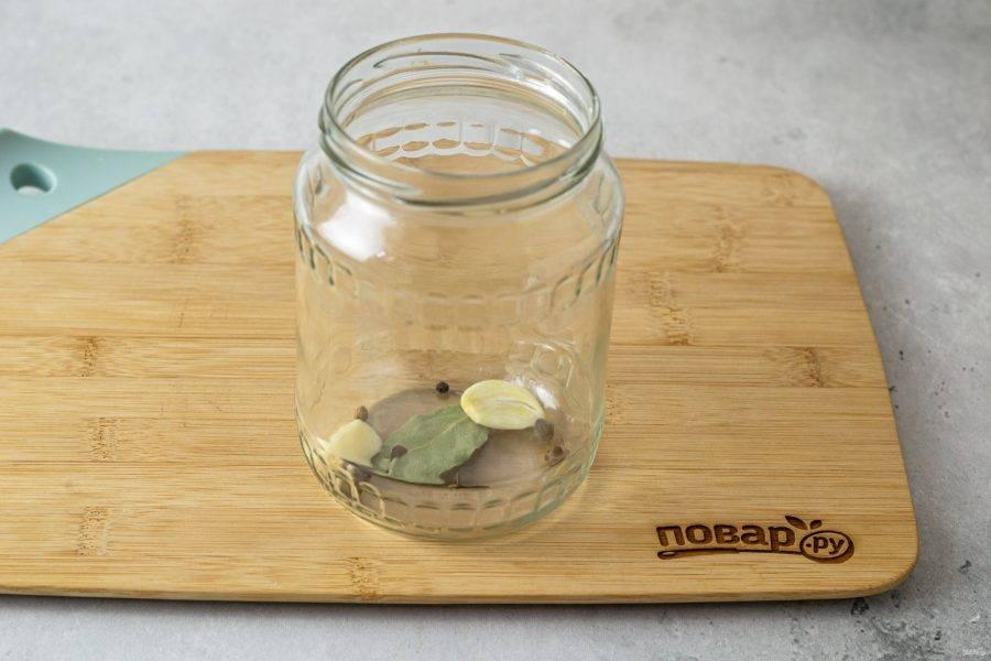 На дно чистой стерилизованной банки выложите очищенный чеснок, перец горошком, гвоздику и лавровый лист.