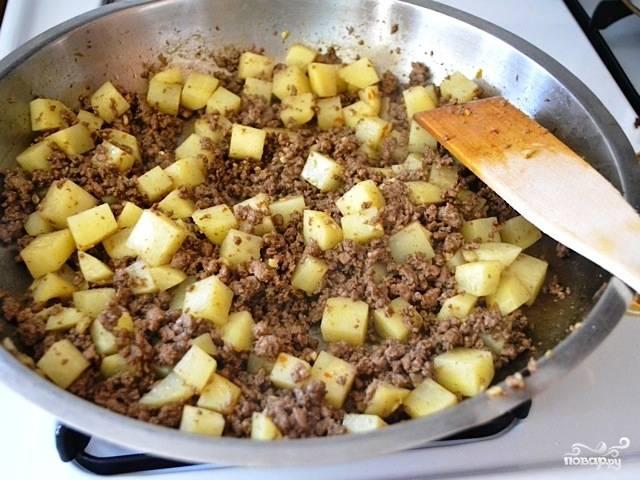 Спустя 2-3 минуты после добавления картофеля добавляем в жаровню бульон и муку. Перемешиваем и готовим на среднем огне. Когда бульон выпарится - пробуем на вкус картофель, если еще сырой - подливаем еще немного бульона или воды.