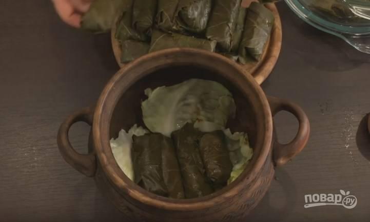 10. Несколько капустных листов положите на сковороду и поджарьте, чтобы они стали чуточку мягче. Выложите их на дно посуды, в которой будут тушиться голубцы. Это могут быть: горшок, утятница, глубокая сковорода. Сложите голубцы в эту посуду.