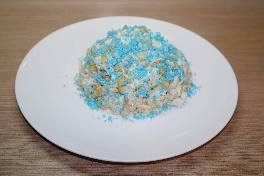 Выложите салат в центр тарелки горкой, посыпьте частью кокосовой стружки, у меня голубая.