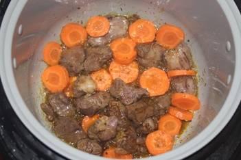 Когда сок из мяса выпарится добавьте морковь. Обжарьте еще несколько минут.