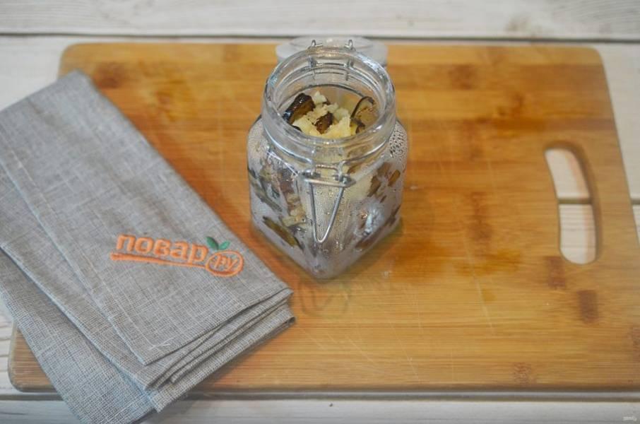 6. Выкладывайте в стерилизованные банки баклажаны, чередуя с чесноком. Затем залейте прокаленным маслом.