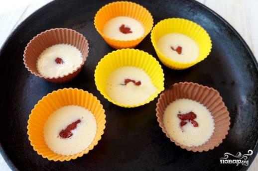 В смазанные формочки наливаем тесто, заполнив их на четверть. Далее кладем по половине чайной ложки варенья. И закрываем еще порцией теста. В итоге формы должны быть наполнены на 2/3.