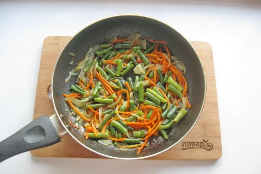 Накройте сковороду крышкой и тушите фасоль с луком и морковью 5-6 минут.