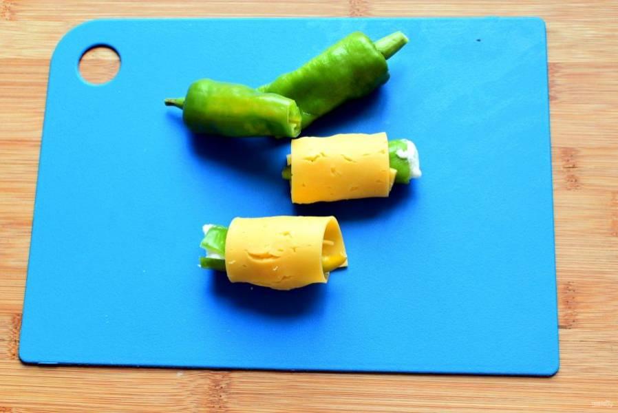 Перцы чили очистите от перегородок и семян, не разрезая, и нафаршируйте мягкой сербской брынзой. Разрежьте перчики пополам и заверните каждый кусочек в тонкий ломтик сыра.