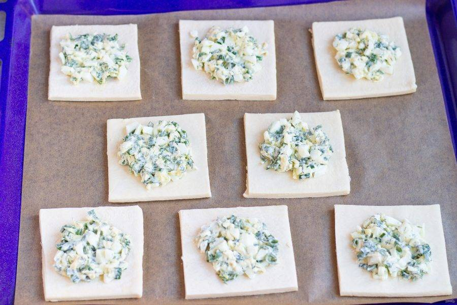 Застелите противень бумагой для выпечки и переложите тесто. Выложите начинку на тесто, оставляя небольшой зазор с краев. Она немного растечется из-за наличия сыра. Поставьте противень в разогретую до 180 градусов духовку на 20-25 мин.