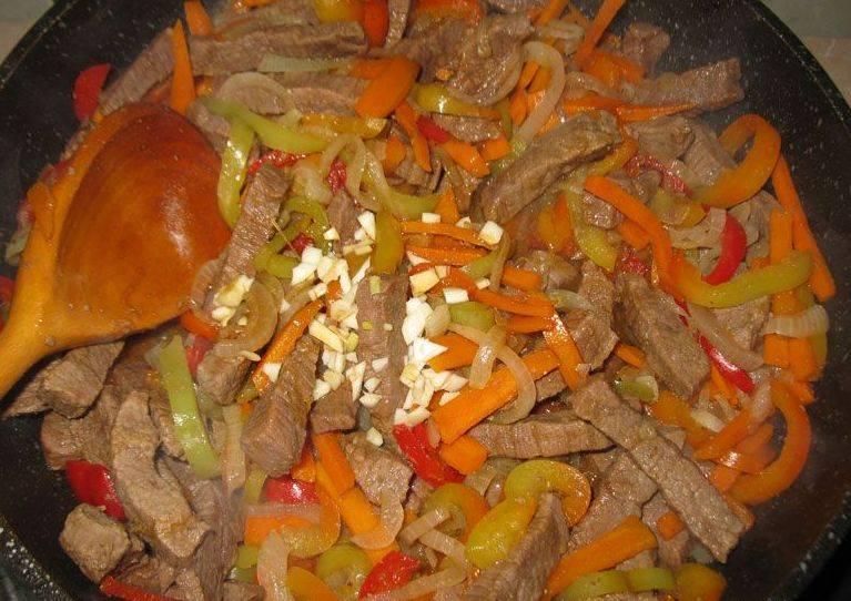 Затем добавляем чеснок, соевый соус, соль по вкусу, перемешиваем все ингредиенты и жарим еще 2 минуты.