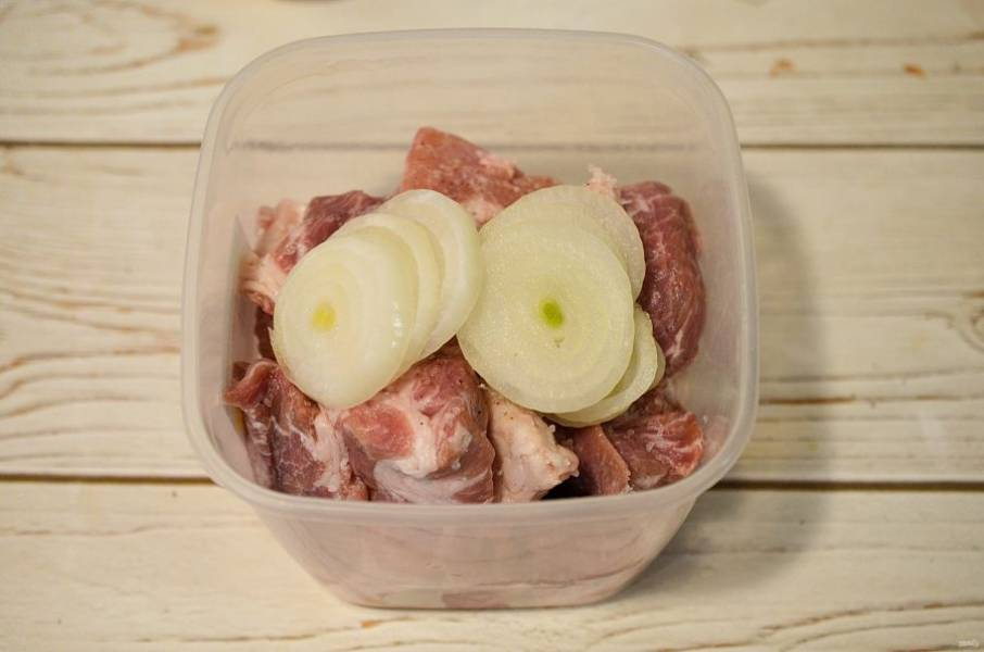 Лук нарежьте кольцами и добавьте к мясу.