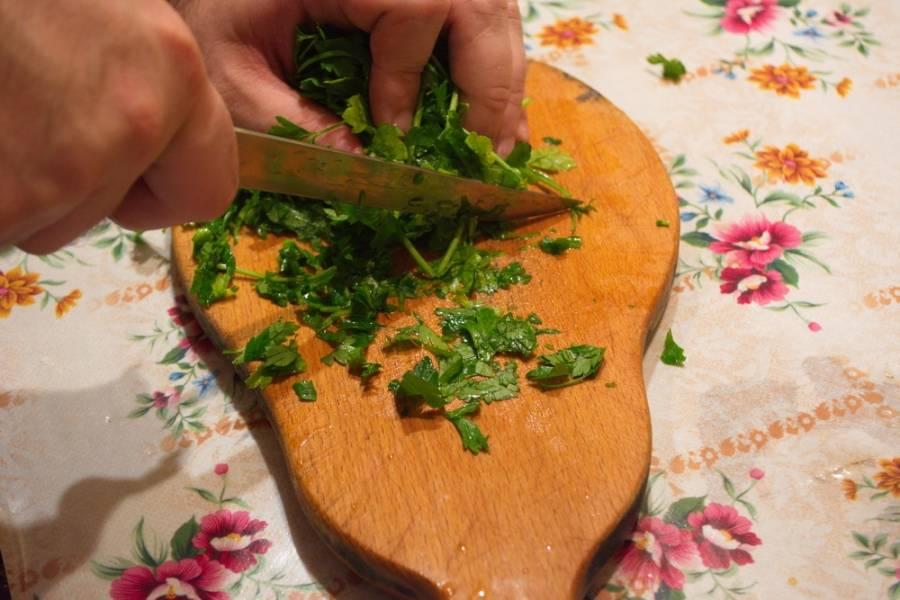 Бумажным полотенцем обсушите зелень, удалив капли воды. Острым ножом измельчите петрушку мелко.