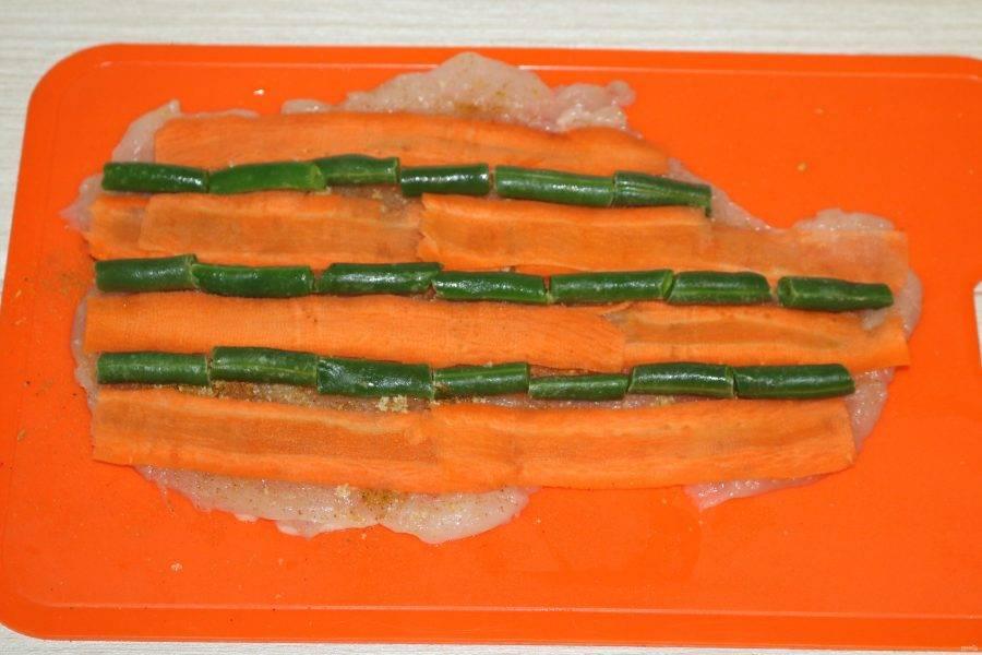 На куриную грудку выложите очищенную морковь, нарезанную слайсами. В промежутках уложите стручковую фасоль.