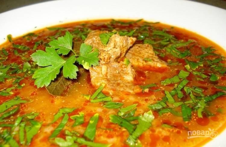 В конце добавьте нарезанное мясо и зелень. Выключите суп. Всыпьте в него специи, перец и соль. Перемешайте. Дайте настояться харчо 20 минут под крышкой. Приятного аппетита!