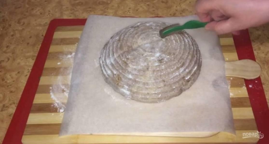 Присыпьте тесто мукой и оставьте на 2-3 часа. Придерживая тесто рукой, переверните корзинку и выложите на пергамент. Аккуратно смахните кисточкой муку, сделайте несколько надрезов и сбрызните водой.