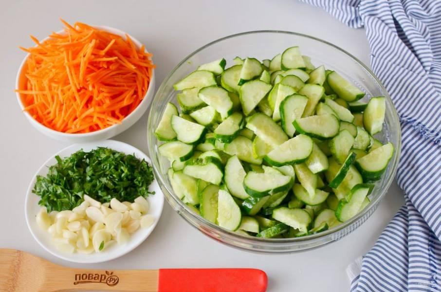 """Порежьте огурцы дольками, как на салат. Морковь натрите на терке для овощей """"по-корейски"""", порубите зелень, чеснок порежьте пластинками."""