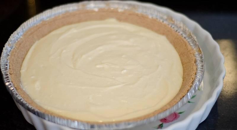 3. Разогрейте духовку до 180 градусов. Нежный творог соедините с сахаром, перемешайте. Добавьте просеянную муку. Вбейте яйцо, влейте сливки и ванильный экстракт. Все как следует перемешайте, чтобы масса была гладкой и однородной. Вылейте в форму и разровняйте.