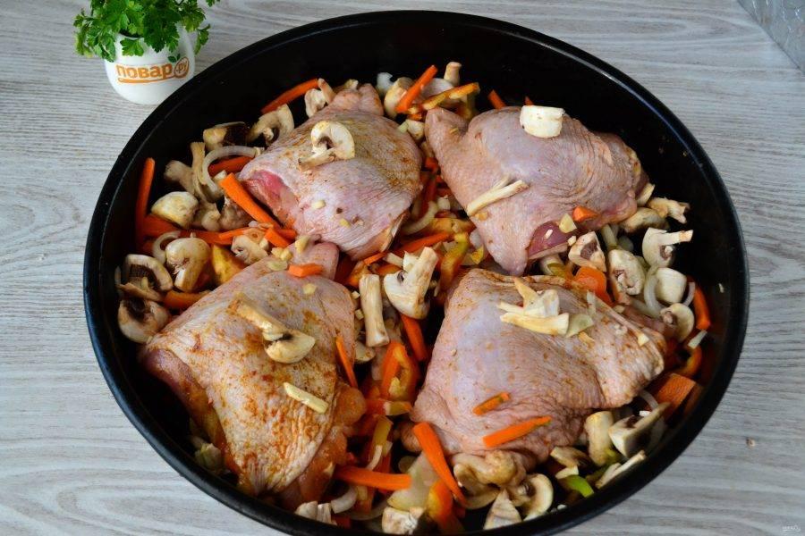 В большую форму для запекания выложите маринованные бедрышки, смешайте грибы с овощами и выложите вокруг мяса. Отправьте в духовку на 20 минут при температуре 180 градусов.