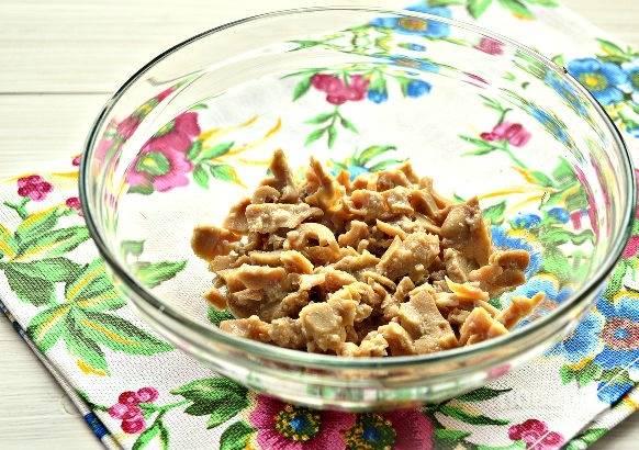 2. Кальмары измельчите немного и выложите в салатник.