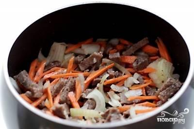 Затем добавьте чеснок, лук и морковь. Перемешайте и продолжайте жарить в течение 7 минут.
