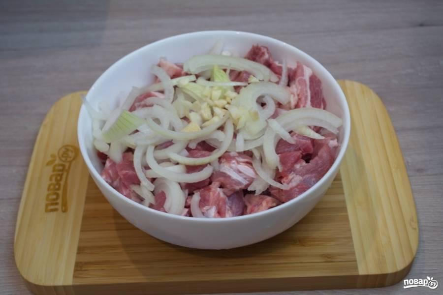 К подготовленному мясу добавьте тонко нарезанный полукольцами репчатый лук. Измельчите чеснок и добавьте к мясу.