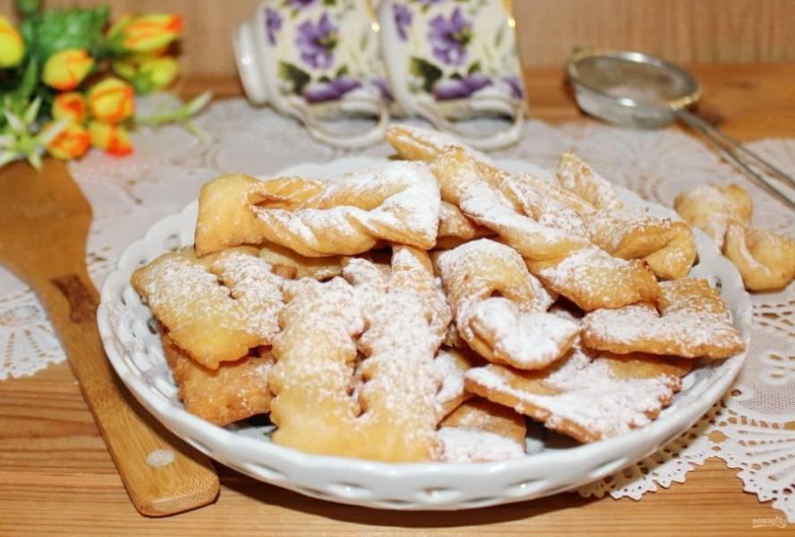 Когда хворост остынет, посыпьте его сахарной пудрой и подавайте к столу.