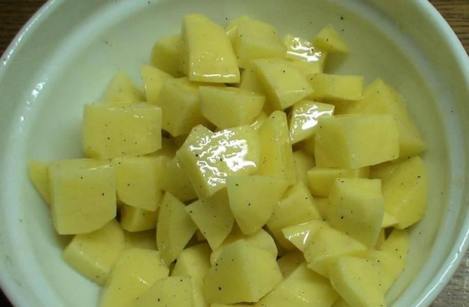 Кубиками нарезаем почищенный картофель. Солим его и также добавляем немного масла.